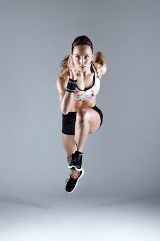 Fit et sportive jeune femme courir sur fond blanc.