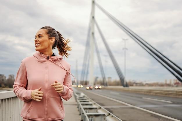 Fit sportive en survêtement jogging sur le pont par temps nuageux.