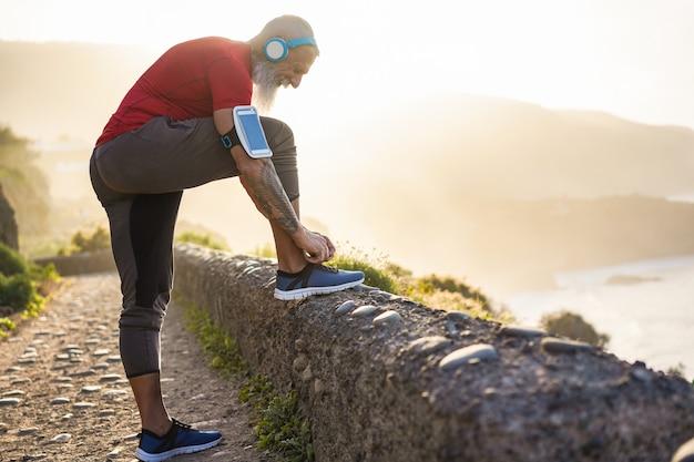 Fit tatouage homme attache ses chaussures de sport en plein air pendant la session de jogging