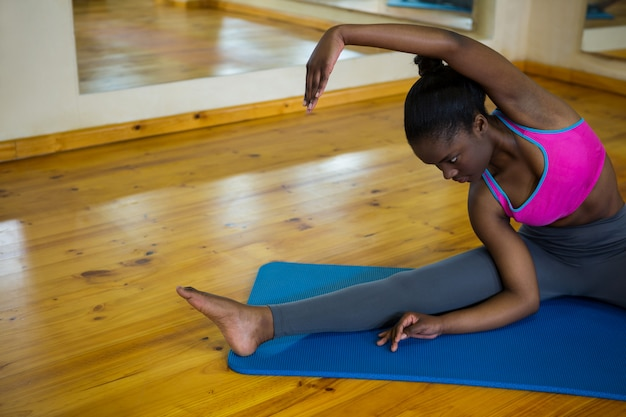 Fit woman doing stretching exercice sur tapis