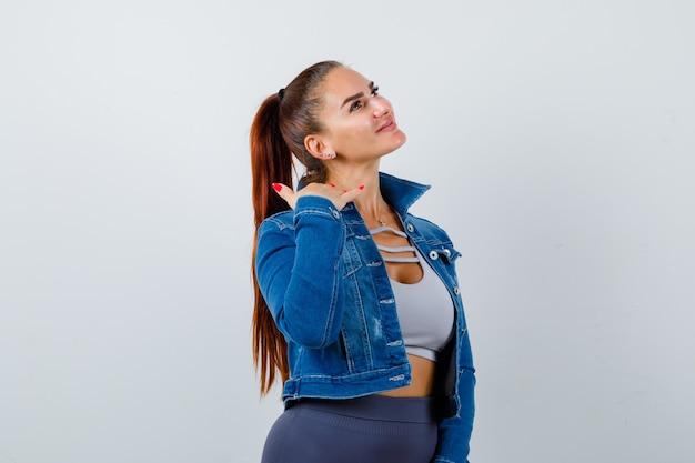 Fit woman montrant le geste du téléphone en crop top, veste en jean, leggings et à la gaieté. vue de face.