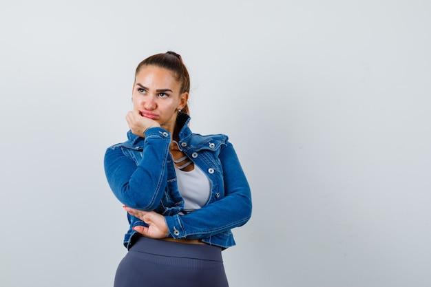 Fit woman penchant le menton sur la paume, pensant à quelque chose dans un crop top, une veste en jean, des leggings et l'air pensif. vue de face.