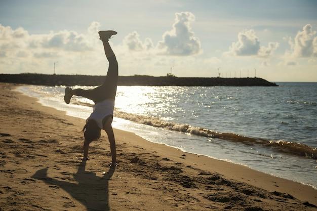 Fit woman somersault par poirier sur la plage au lever du soleil