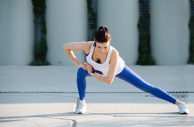 Fit woman stretching sur un pavage en béton faisant des salons latéraux