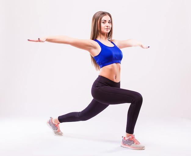 Fit woman stretching sa jambe pour se réchauffer isolé sur fond blanc