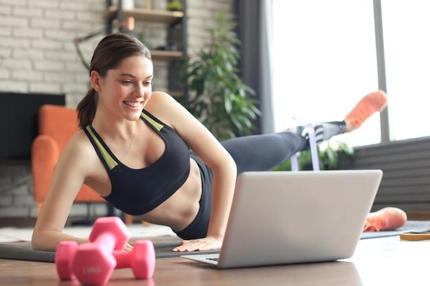 Fitness belle femme mince faisant une planche latérale avec une bande de résistance et regardant des tutoriels en ligne sur un ordinateur portable, s'entraînant dans le salon. restez à la maison activités.