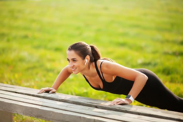 Fitness belle jeune femme faisant des exercices dans le parc