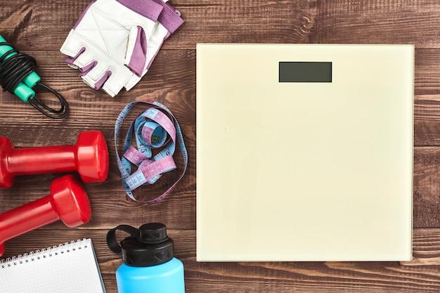 Fitness et concept de fond de mode de vie actif sain. équipement de l'athlète: haltère, bouteilles d'eau de sport, corde à sauter, gants de sport, échelle de poids sur fond en bois. mise à plat. espace pour le texte.