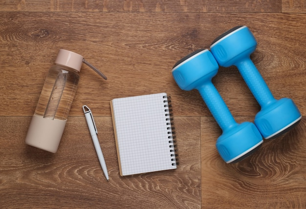 Fitness, concept de mode de vie sain. haltères, bouteille d'eau, cahier sur le sol. vue de dessus