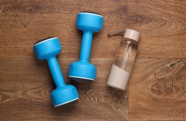 Fitness, concept de mode de vie sain. haltères, bouteille d'eau sur le sol. vue de dessus