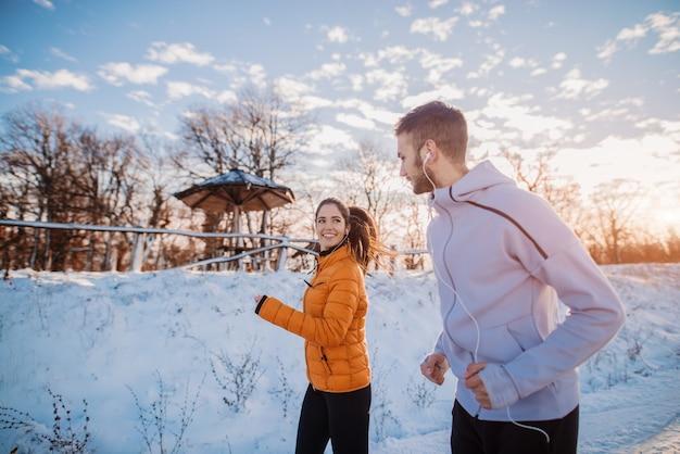 Fitness couple hiver matin exercice à la montagne enneigée.