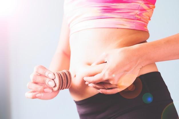 Fitness féminin dans le soutien-gorge de sport rose serre sa taille grasse et un goûter d'autre part avec un espace de copie