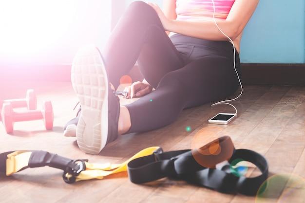 Fitness féminin reposant et relaxant après la séance d'entraînement. femme assise sur le parquet. sport, fitness, mode de vie sain