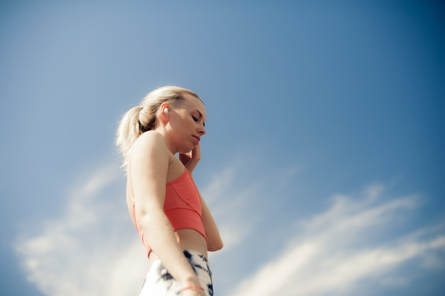 Fitness femme écoute la musique dans les écouteurs sans fil. belle fille de coupe sportive