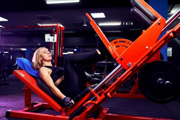 Fitness femme faisant des exercices de fentes pour la formation de muscle jambe dans la salle de gym