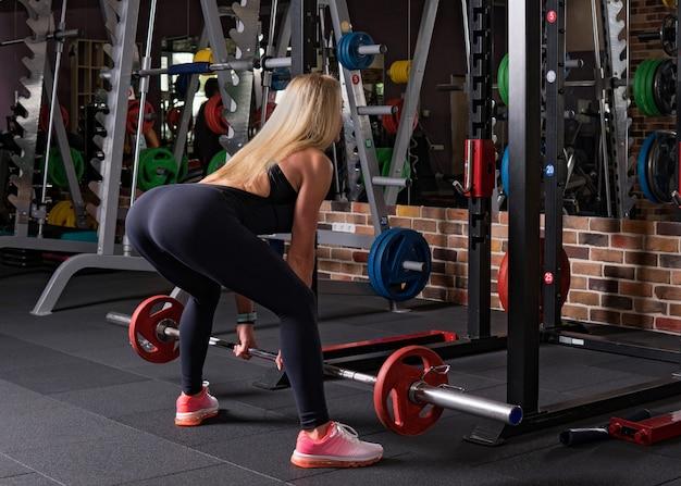 Fitness femme faisant de la levée de terre dans la salle de gym