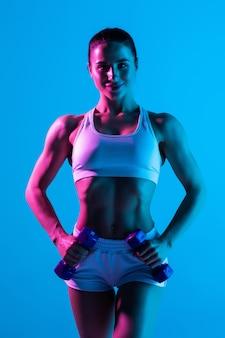 Fitness femme avec haltère fit corps mince abs isolé sur un fond bleu clair