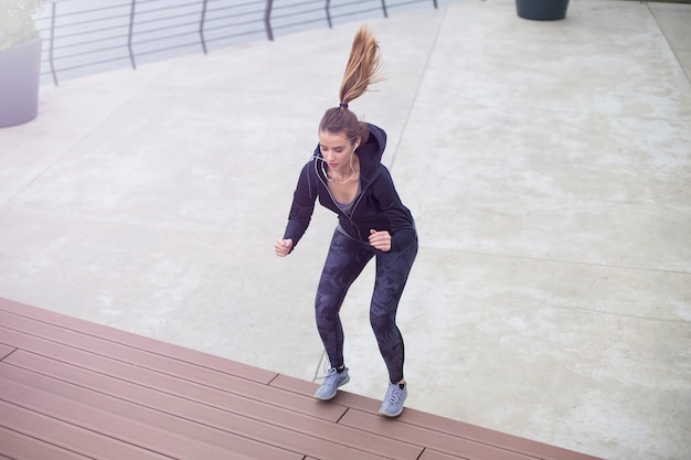Fitness femme sautant en plein air en milieu urbain