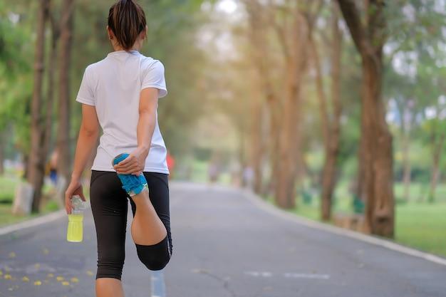 Fitness femme se étirant dans le parc, réchauffement des femmes prêtes pour le jogging