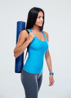 Fitness femme tenant un tapis de yoga