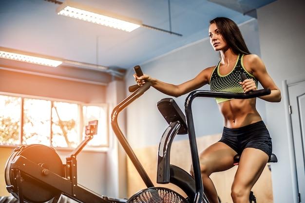 Fitness femme utilisant air bike pour entraînement cardio au gymnase de crossfit.