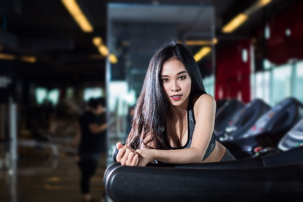 Fitness femmes asiatiques effectuant des exercices entraînant la course sur tapis roulant