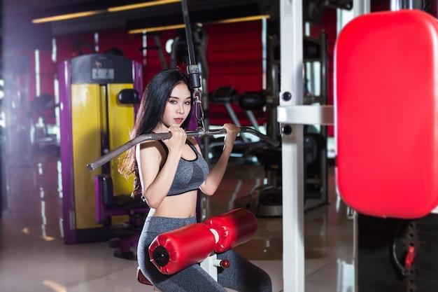 Fitness femmes asiatiques effectuant des exercices entraînant les muscles de l'épaule et du thorax dans un club de sport et de remise en forme.