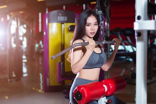 Fitness femmes asiatiques effectuant des exercices d'entraînement des muscles de l'épaule et de la poitrine à l'intérieur d'un gymnase de sport