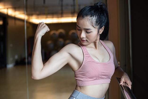 Fitness femmes montrent les muscles des bras dans la salle de gym.