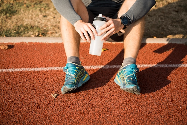 Fitness garçon tenant une bouteille d'eau