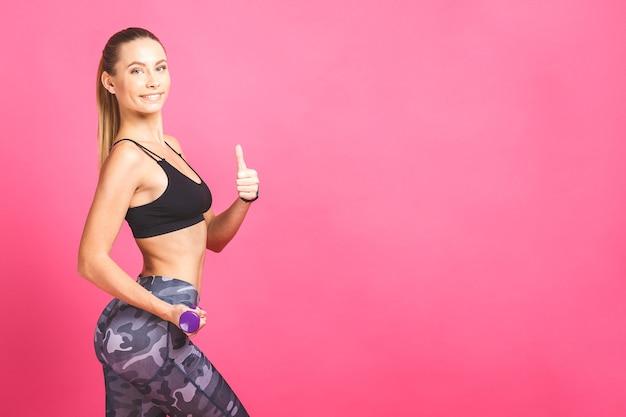 Fitness girl fit femme avec des haltères, faire de l'exercice avec des haltères formation avec des poids isolés sur fond rose