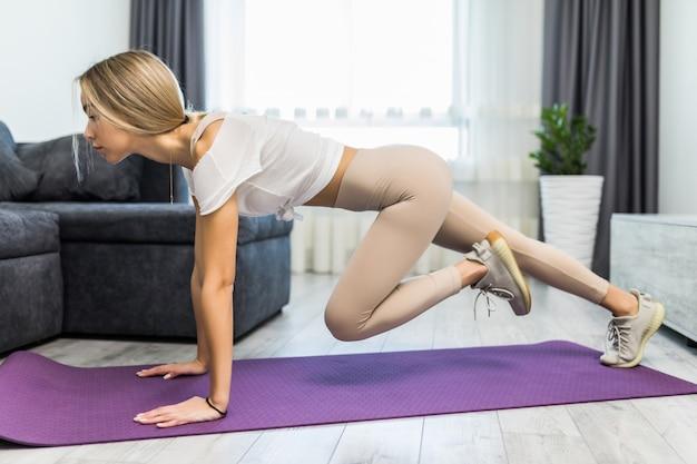Fitness girl watch laptop aerobics regime workout video stretch leg hips squats wear panties on mat floor at home