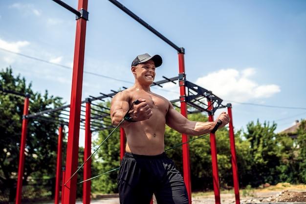 Fitness homme formation poitrine avec des bandes de résistance à la cour de gym de rue. entraînement en plein air. body workout avec du matériel à l'extérieur. accessoire élastique en caoutchouc.