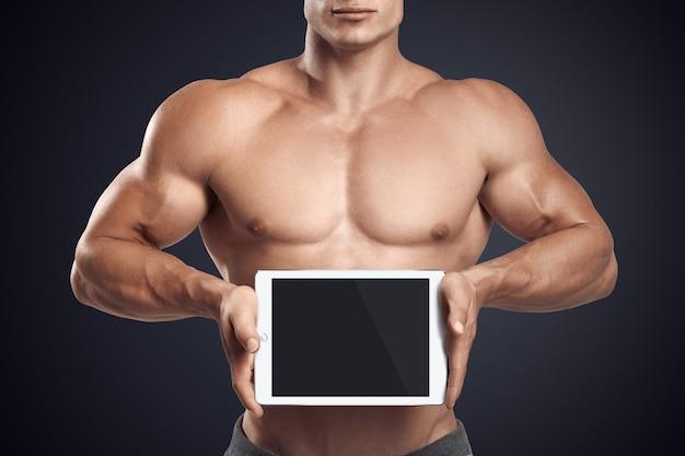 Fitness homme tenant une tablette numérique horizontalement avec écran blanc