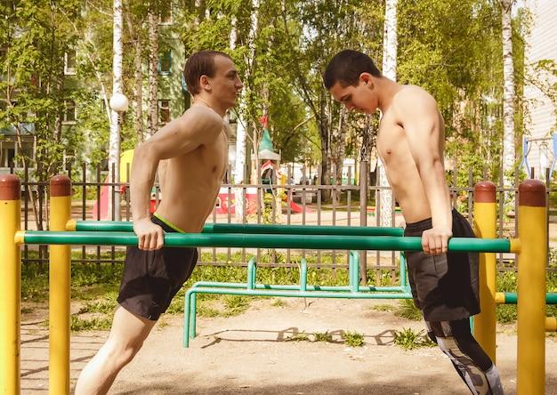 Fitness hommes au bar. faire de l'exercice en plein air dans le parc. street workout.