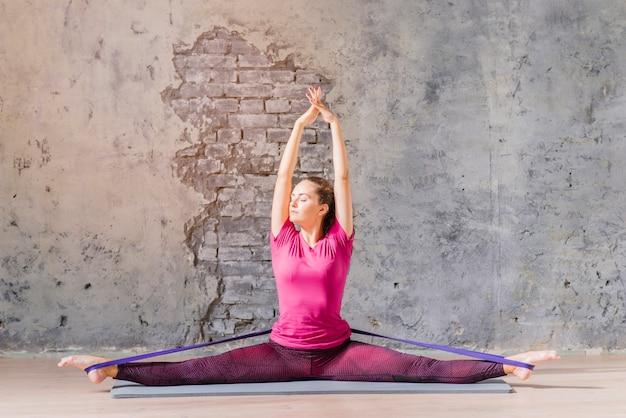 Fitness jeune femme faire des exercices avec bande de résistance contre le mur gris
