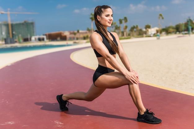 Fitness jeune femme faisant des exercices de fentes sur la plage
