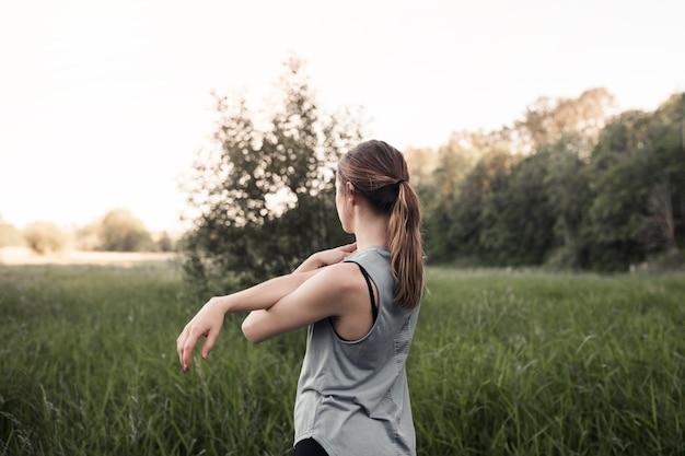 Fitness jeune femme qui s'étend de sa main debout dans l'herbe verte