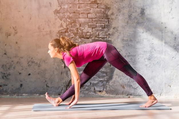 Fitness jeune femme qui s'étend ses jambes