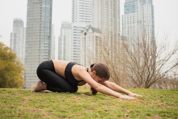 Fitness jeune fille qui s'étend en plein air