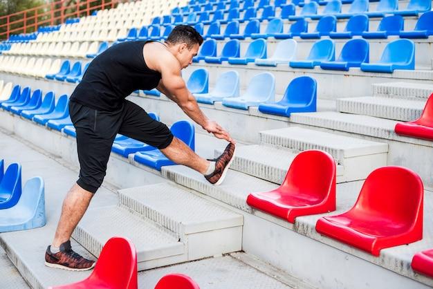 Fitness jeune homme qui s'étend de sa jambe sur le gradin