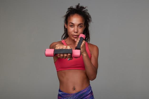 Fitness jeune modèle à la peau sombre avec de longs cheveux bruns bouclés faisant des exercices avec des haltères tout en posant. concept de sport et de mode de vie sain
