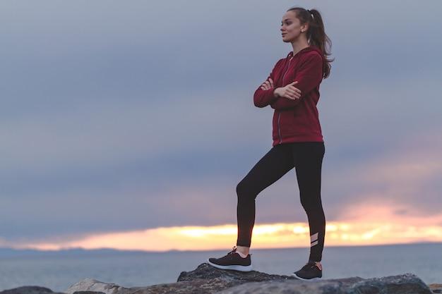 Fitness jolie femme en baskets grimpant sur un rocher après une séance d'entraînement et regardant au loin au coucher du soleil. sports et mode de vie actif