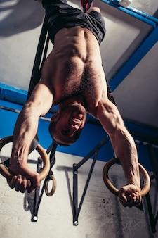 Fitness mâle suspendu à l'envers sur des anneaux de gymnastique