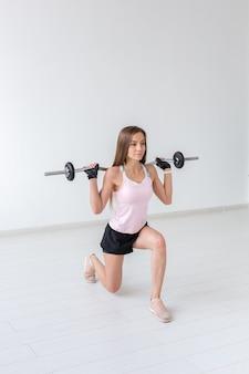 Fitness, sport, concept de personnes - jeune femme en costume de sport, des gants s'accroupissent avec un bar.