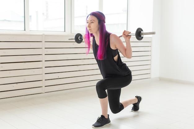 Fitness, sport, concept de personnes - une jeune femme en costume de sport s'accroupit avec un bar.