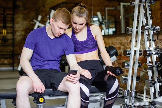 Fitness, sport, technologie et amaigrissement - femme et entraîneur personnel avec smartphone et gourde dans la salle de sport