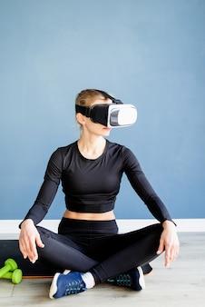 Fitness, sport et technologie. jeune femme athlétique portant des lunettes de réalité virtuelle assis sur un tapis de fitness