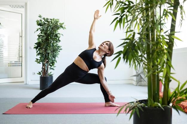 Fitness stretching, femme mûre portant des vêtements de sport travaillant dans un club de sport, exercice de flexion du dos