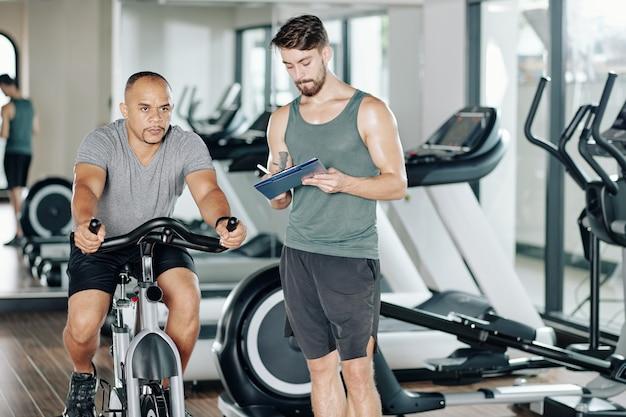Fitness trainer écrit dans un document lorsque son client essaie un nouvel entraînement cardio et roule vite sur un vélo stationnaire
